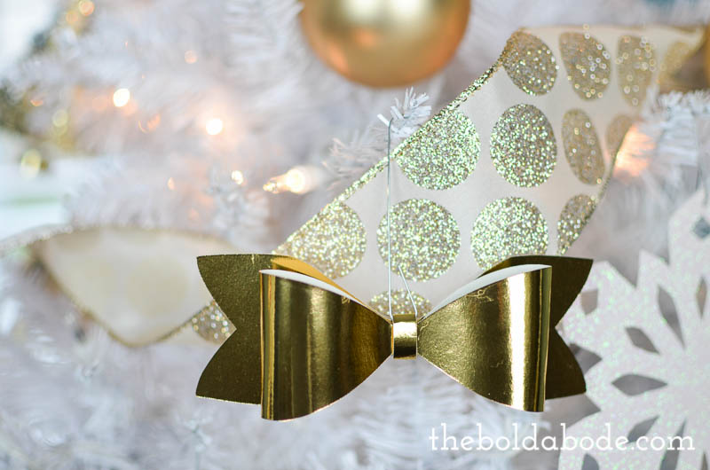 Make your own mini bow ornaments with some pretty, glittery paper! They are so pretty and light on your holiday budget! #christmas #christmasornaments #paperbows #paperornaments #gold #glitter #