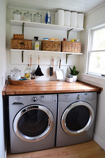 This room is clean and simple with the stream-lined shelving and gorgeous wood shelf above the washer and dryer units. To me this leans towards a more modern almost Scandinavian type feel.
