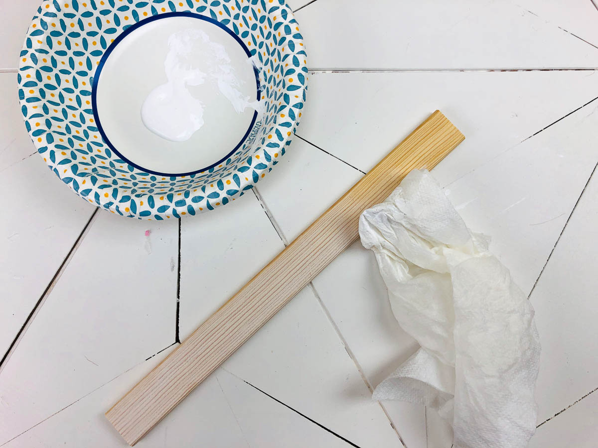 white paint and wood slat with damp paper towel