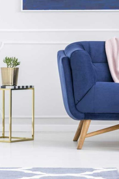 white room with blue couch, pink blanket, gold side tables