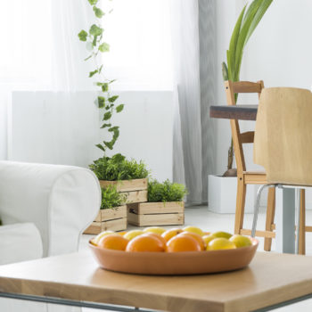 clean living room with white couch and coffee table with oranges in a tray