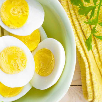 bowl of boiled eggs cut in half with a yellow napkin and green garnish