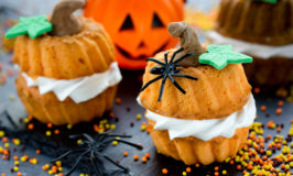 mini pumpkin cakes decorated with plastic spiders