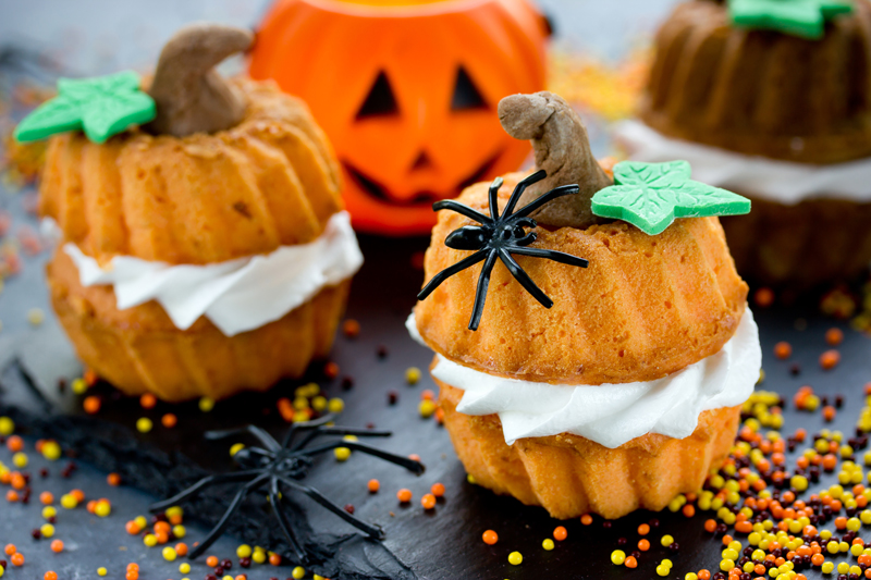 mini pumpkin cakes decorated with plastic spiders